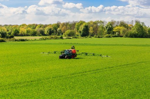 59333206 - tractor spraying glyphosate pesticides on a corn field